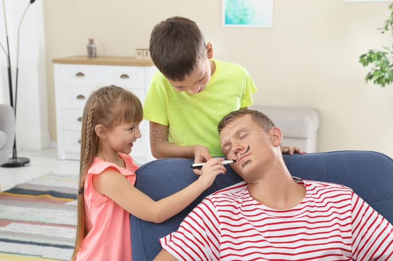 Children painting their father`s face while he sleeping stock photo