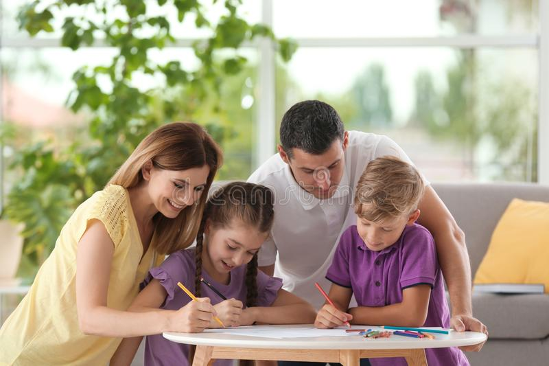 Children with parents drawing at table indoors stock photo