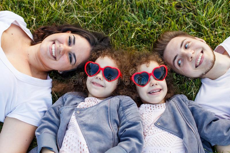 Children with parents in the park. Cute family haming fun in nature. Twin toddler sisters holding parents. Happy family concept stock photo