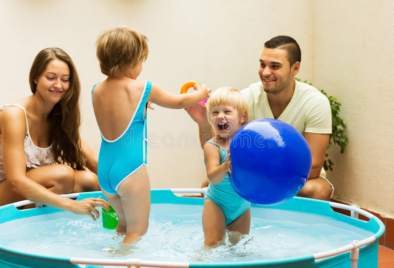 Children and parents playing in pool stock photos