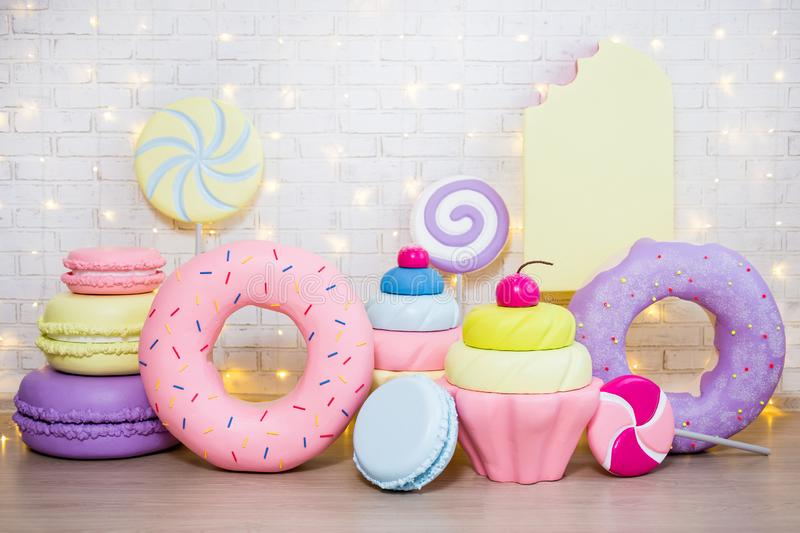Children party background - set of huge artificial sweets and pastry decorations over white brick wall. With lights royalty free stock image