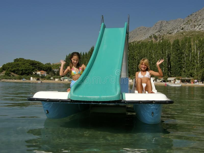 Children on pedal boat at sea stock photo