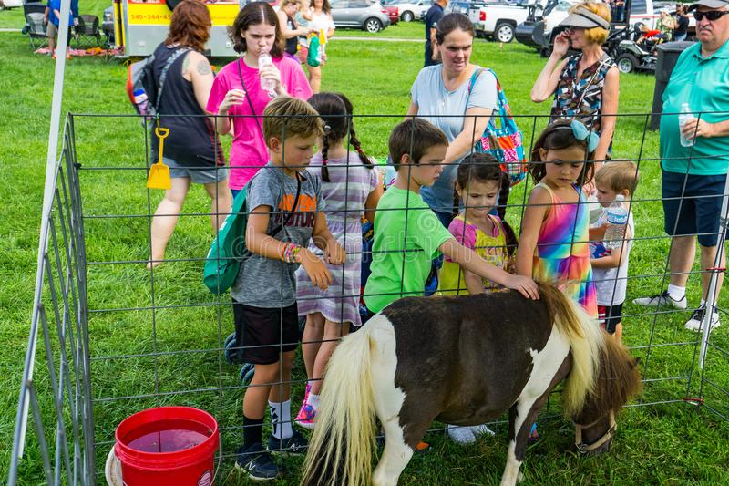 Children Petting Miniature Pony at the Petting Zoo at the Annual Touch-A-Truck royalty free stock image