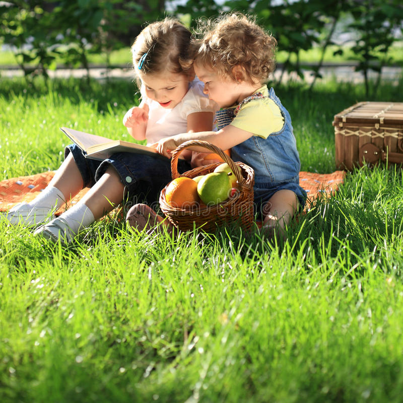 Children on picnic. Children reading the book on picnic in summer park