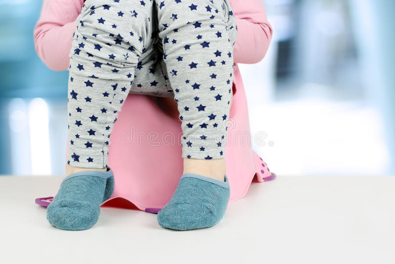 Children& x27; piernas de s que cuelgan abajo de un cámara-pote en un fondo azul fotografía de archivo libre de regalías