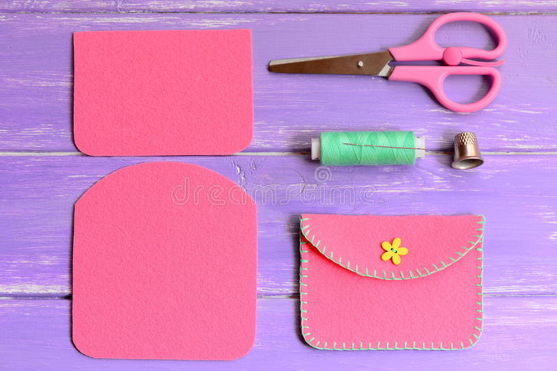 Children pink felt purse with yellow flower wooden button. Scissors, thread, needle, thimble on a wooden table. Purse sewing pattern. Purse tutorial. Felt purse stock image
