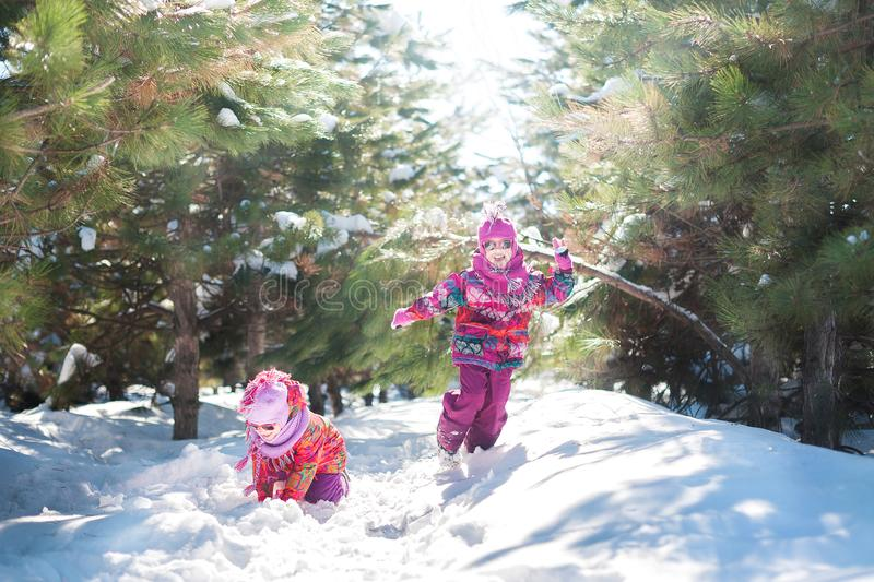 Children in pink suits jump in the snow in winter. Children`s winter holidays stock photo