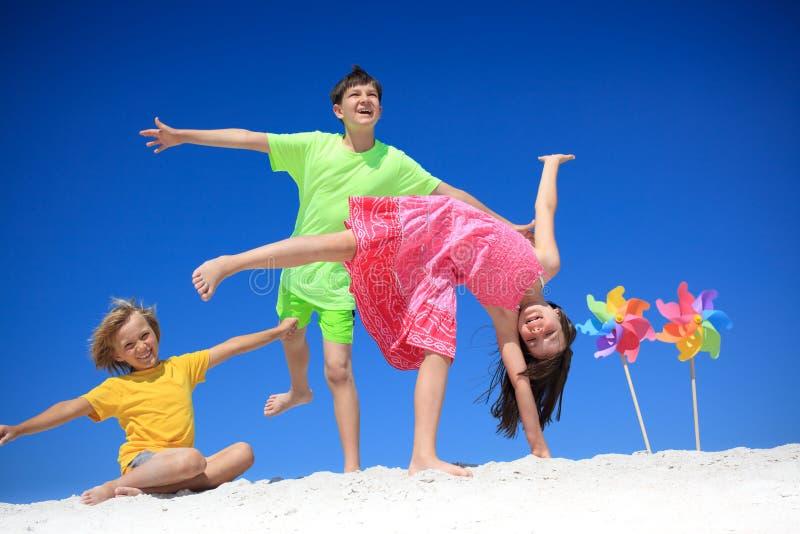 Children with pinwheels on beach royalty free stock photos