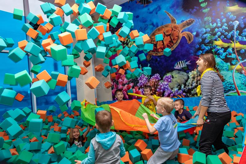 Children play with the animator in the entertainment center. Children play in the pool with soft cubes. Cheboksary, Russia, 10/20/. Children play with the stock images