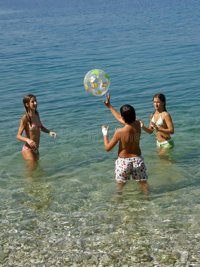 Children play with a ball in sea stock images