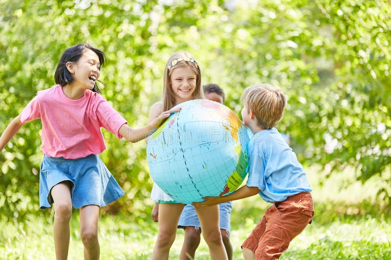 Children play ball in summer with globe ball royalty free stock photos