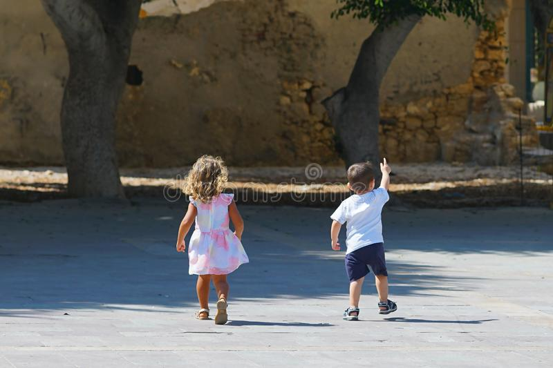 children play carefree in a small square in the historic center of Heraklion stock photo