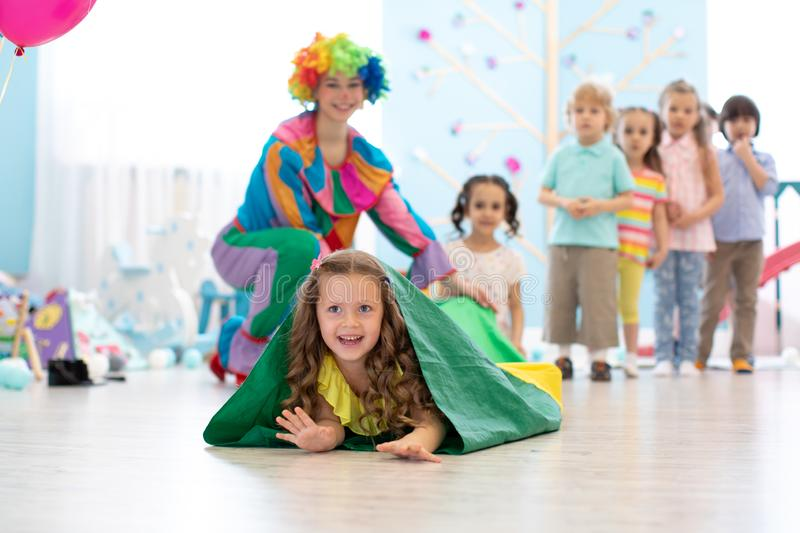 Children play with clown on birthday party in entertainment centre stock photo