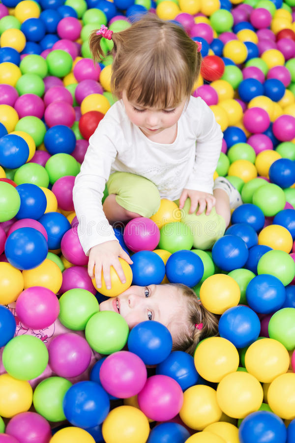 Children play in colorful balls stock photography