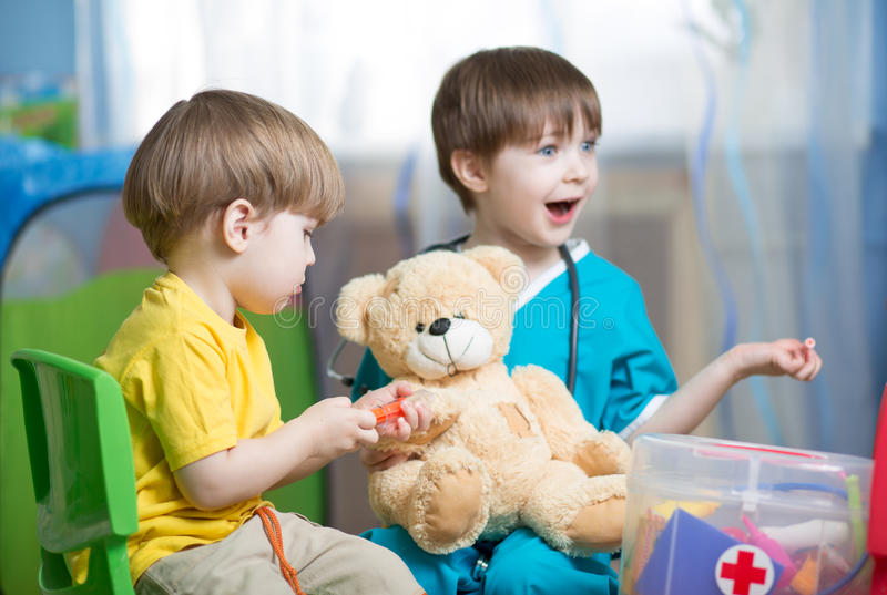 Children play doctor with plush toy stock photography