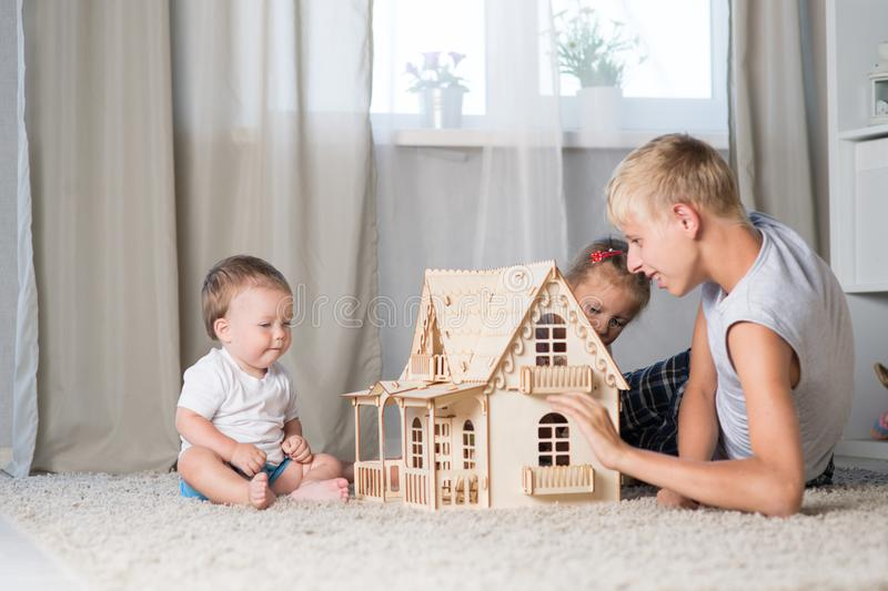 Children play with a doll house royalty free stock image