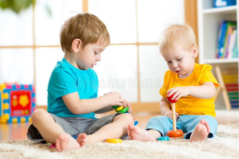 Children play with educational toys in preschool or kindergarten. Toddler kid and baby build pyramid toys at home or stock images