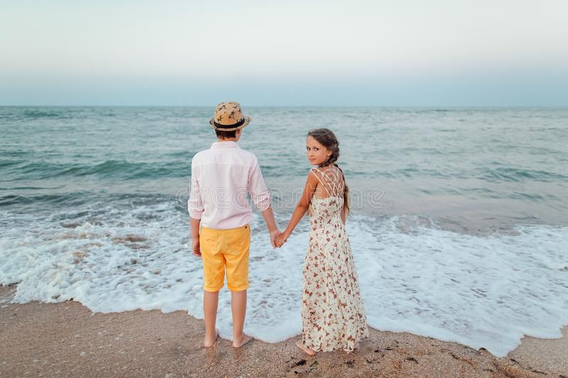Children play and have fun on the beach. Romantic story on the seafront. Boy and girl are standing on the beach holding hands royalty free stock images