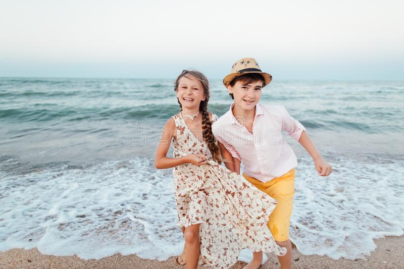 Children play and have fun on the beach. Romantic story on the seafront. The girl and the guy run away from the wave. Children play and have fun on the beach stock images