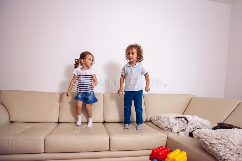 Children play and have fun jumping on the bed. stock photos