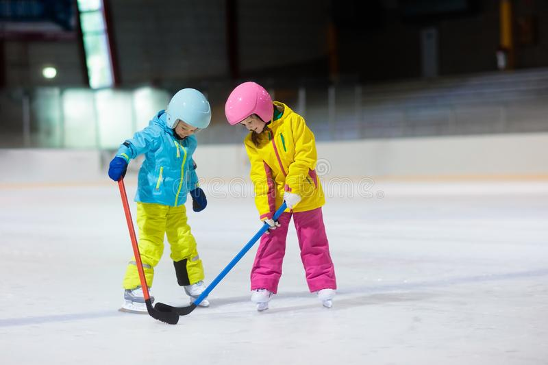 Children play ice hockey. Kids winter sport. Children play ice hockey on indoor rink. Healthy winter sport for kids. Boy and girl with hockey sticks hitting royalty free stock photo