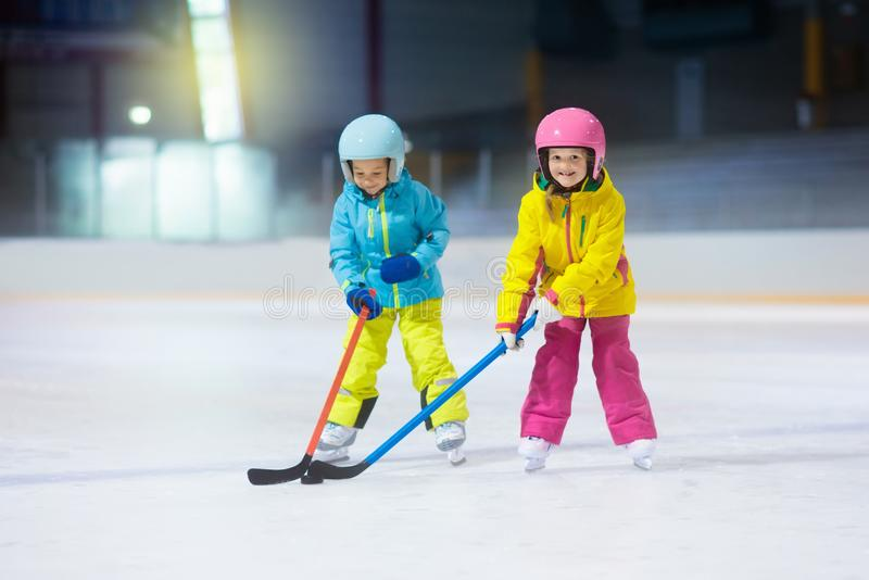 Children play ice hockey. Kids winter sport. Children play ice hockey on indoor rink. Healthy winter sport for kids. Boy and girl with hockey sticks hitting royalty free stock image