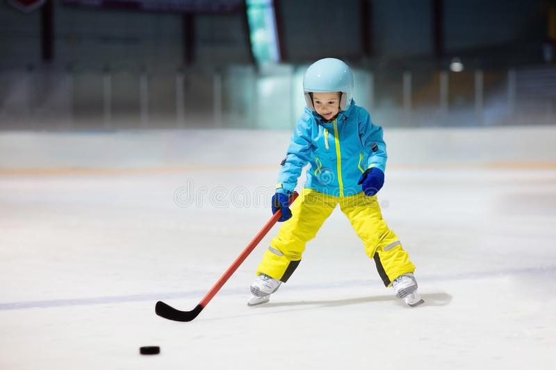 Children play ice hockey. Kids winter sport. Children play ice hockey on indoor rink. Healthy winter sport for kids. Boy with hockey stick hitting puck. Child royalty free stock photos