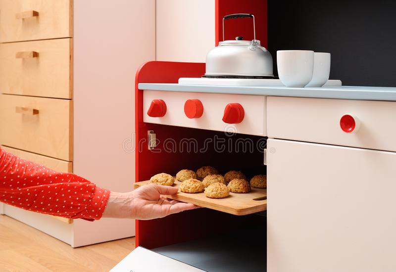 Children play in kitchen. Baking homemade cookies in toy oven stock image