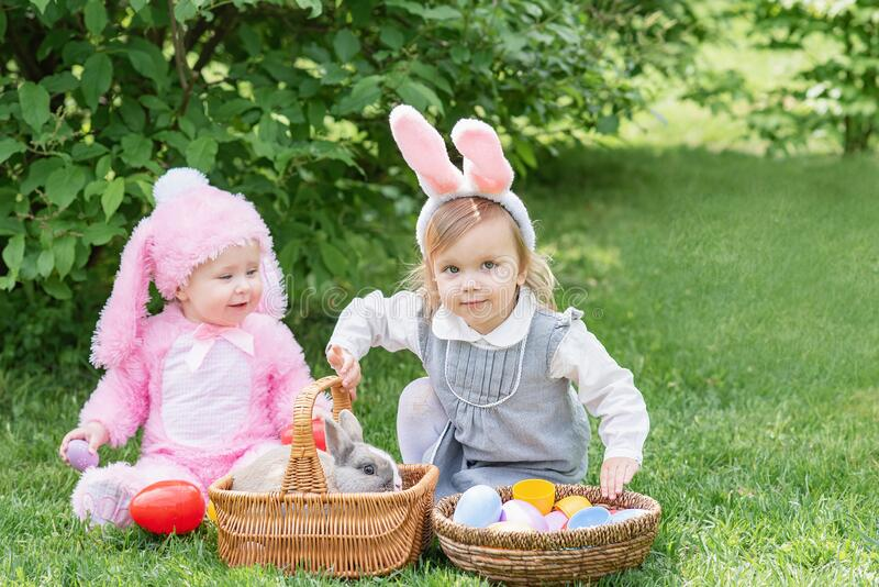 Children play with real rabbit. Laughing child at Easter egg hunt with pet bunny stock photography