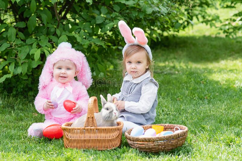 Children play with real rabbit. Laughing child at Easter egg hunt with pet bunny royalty free stock photo