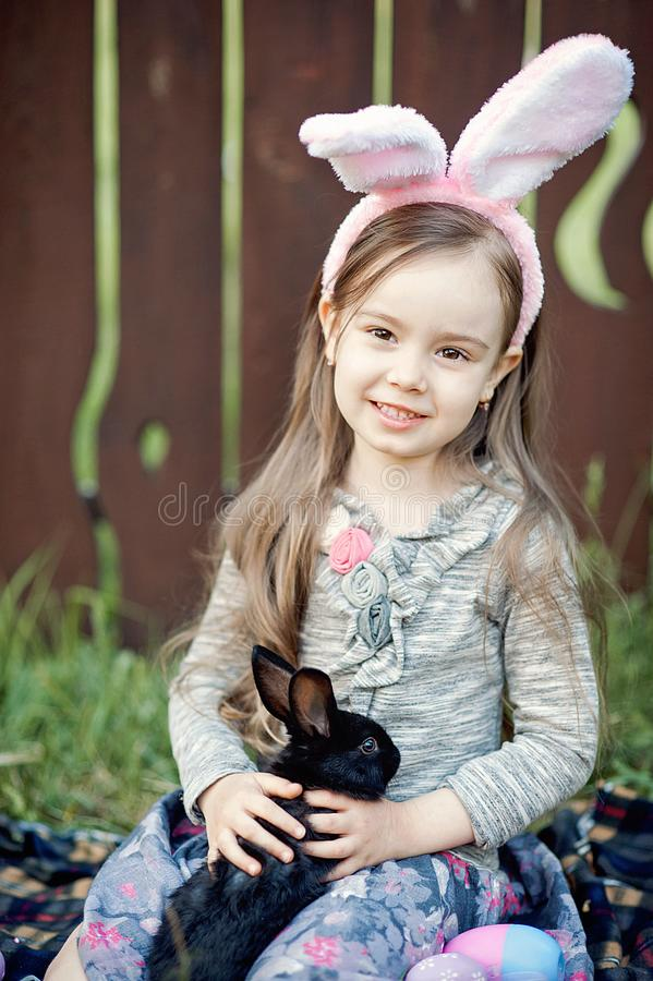 Children play with real rabbit. Laughing child at Easter egg hunt with white pet bunny. Little toddler girl playing with animal in royalty free stock photography