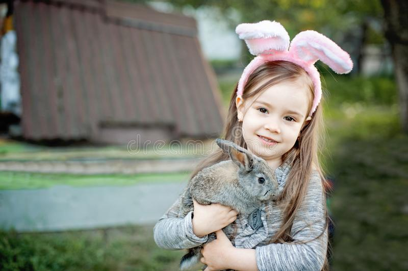 Children play with real rabbit. Laughing child at Easter egg hunt with white pet bunny. Little toddler girl playing with animal in stock image