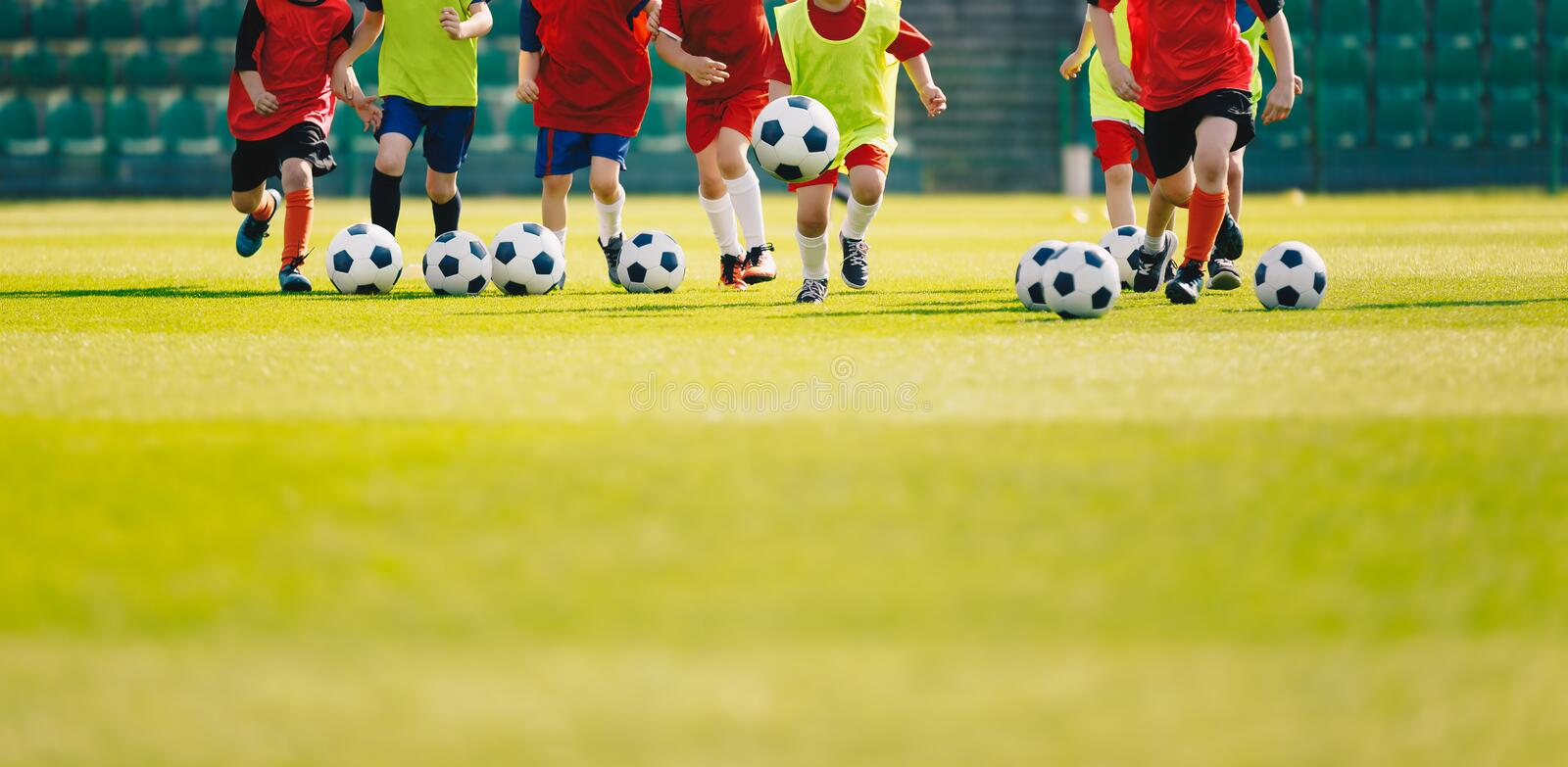 Children play soccer at grass sports field. Football training for kids. Children running and kicking soccer balls at soccer pitch. Soccer background with copy stock photos