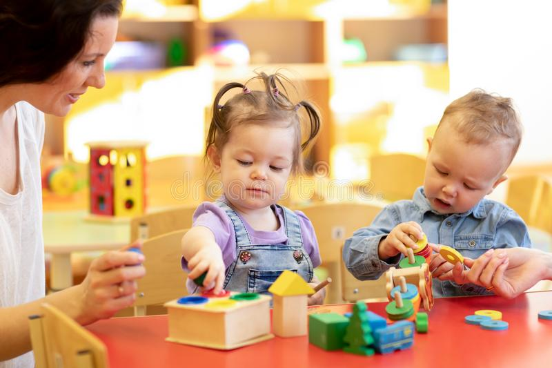 Children play with a teacher in the nursery royalty free stock images