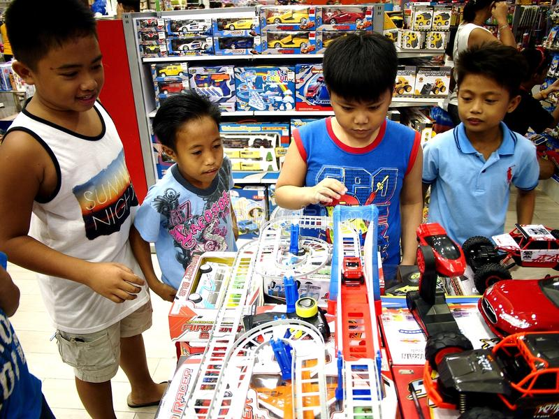 Children play with toys in a toy store in SM City mall in Taytay City, Philippines. TAYTAY CITY, PHILIPPINES - JULY 15, 2017: Children play with toys in a toy stock images