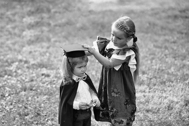 Children play in the university. Cute girl dressing small boy in graduation hat and robe. Children play in the university. Cute little girl with long hair in stock photo