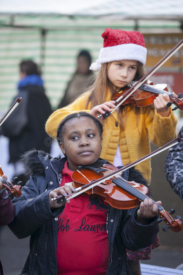 Children play the violin at the Christmas Fair. LONDON, UK-NOVEMBER 16: children play the violin at the Christmas Fair. Broadway market. November 16, 2016 in royalty free stock photos
