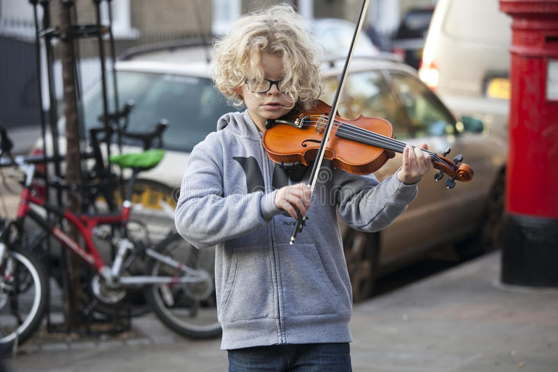 Children play the violin at the Christmas Fair. LONDON, UK-NOVEMBER 16: children play the violin at the Christmas Fair. Broadway market. November 16, 2016 in royalty free stock images