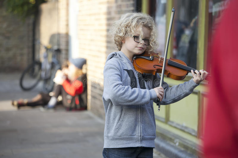 Children play the violin at the Christmas Fair. LONDON, UK-NOVEMBER 16: children play the violin at the Christmas Fair. Broadway market. November 16, 2016 in stock photos