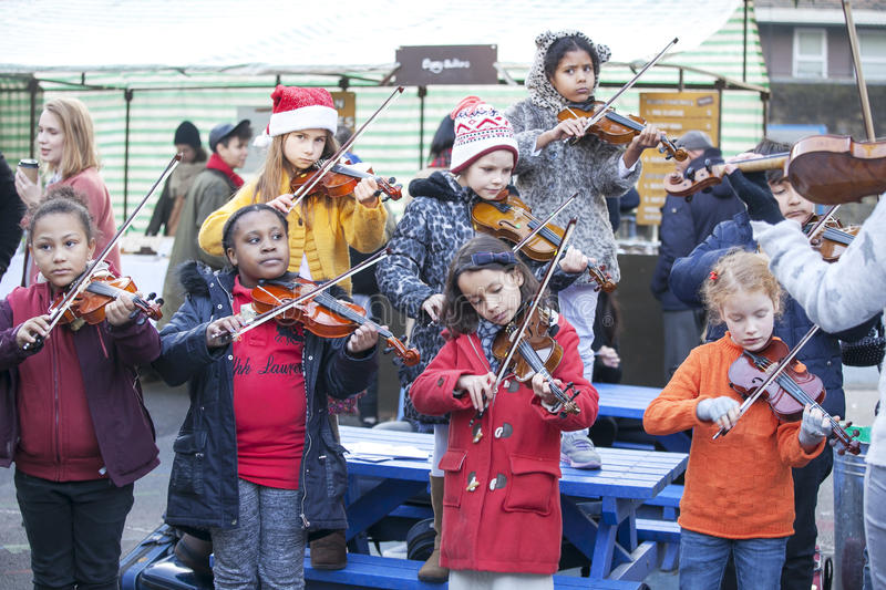 Children play the violin at the Christmas Fair. LONDON, UK-NOVEMBER 16: children play the violin at the Christmas Fair. Broadway market. November 16, 2016 in stock photo
