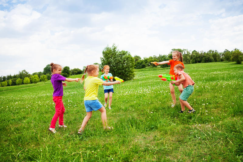 Children play with water guns on a meadow. Children playing with water guns on a meadow with dandelions royalty free stock photography