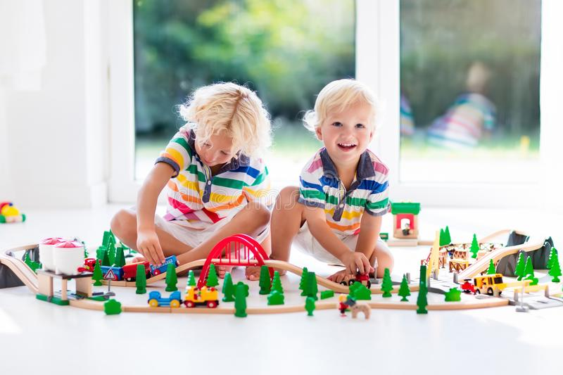 Children play wiht toy train. Kids wooden railway. Kids play with toy train railway. Children playing with wooden trains. Toys for little boy. Two brothers stock image