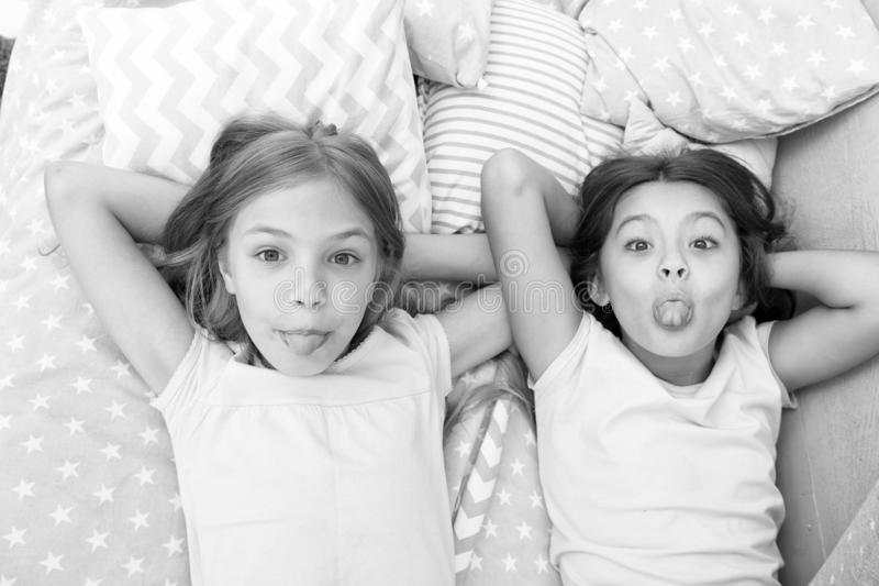Children playful cheerful mood having fun together. Pajama party and friendship. Sisters happy small kids relaxing in. Bedroom. Friendship of small girls stock photo