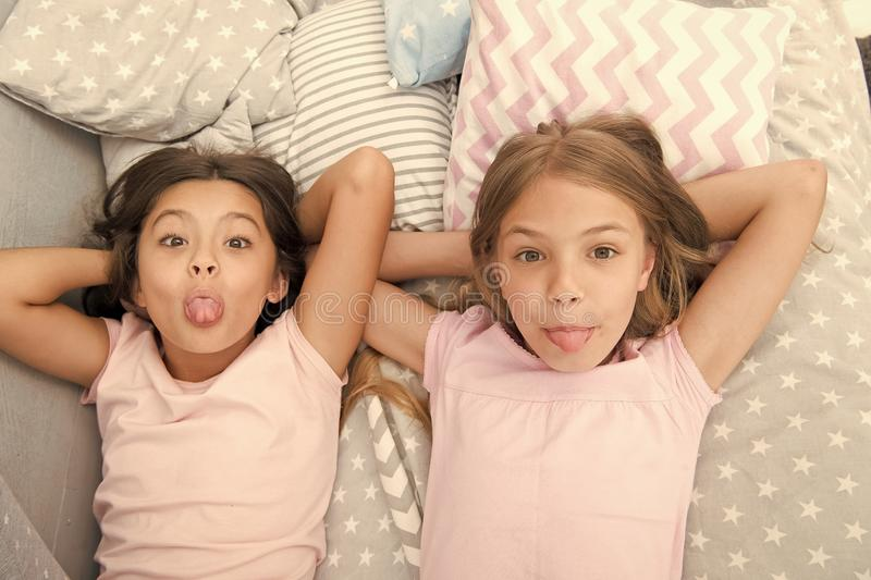 Children playful cheerful mood having fun together. Pajama party and friendship. Sisters happy small kids relaxing in. Bedroom. Friendship of small girls royalty free stock photos
