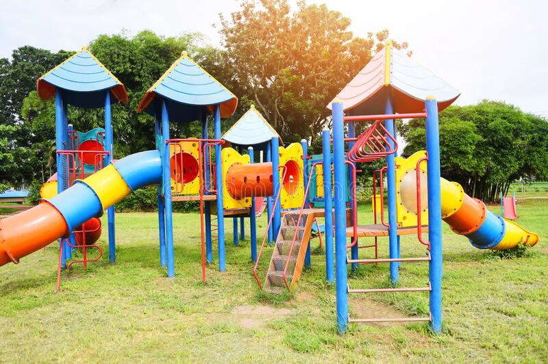 Children playground on outdoors activities in the garden with green trees background - Colorful playground on yard in the park. Children playground on outdoors royalty free stock photography