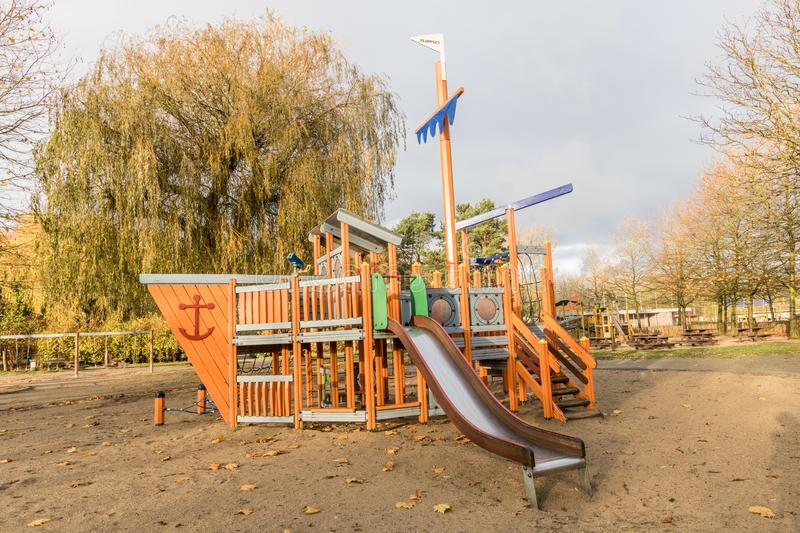 Children playground in public park. Surrounded by green trees in belgium.children run,slide,swing royalty free stock photo