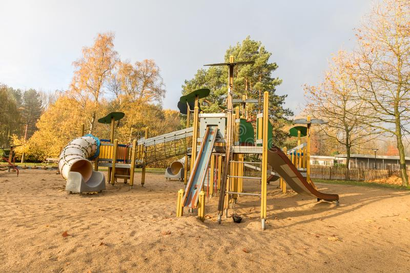 Children playground in public park. Surrounded by green trees in belgium.children run,slide,swing royalty free stock photography