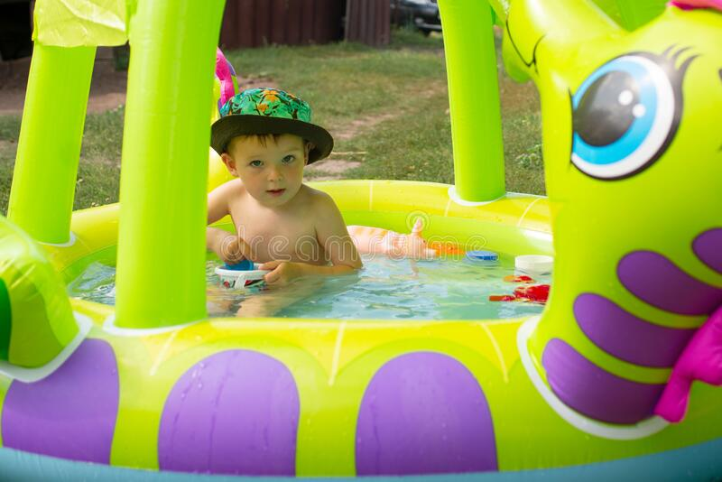 Children playing and active leisure - swimming pool concept. Child having fun in summertime. Little child boy having fun in the royalty free stock photography