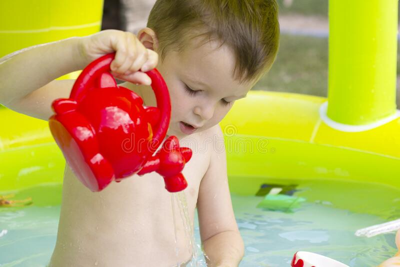 Children playing and active leisure - swimming pool concept. Child having fun in summertime. Little child boy having fun in the royalty free stock images