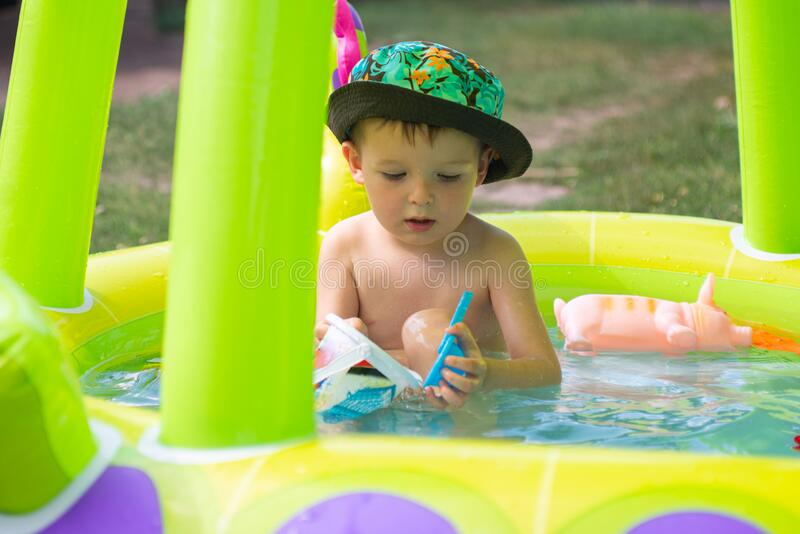 Children playing and active leisure - swimming pool concept. Child having fun in summertime. Little child boy having fun in the stock images